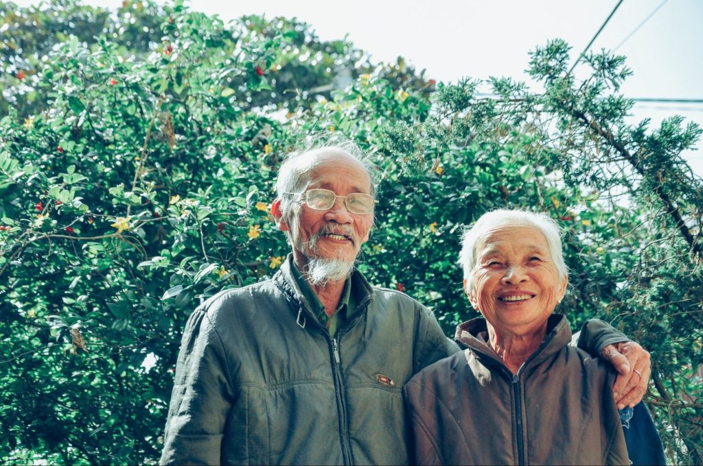 Elderly couple walking in nature. Exercise for arthritis - Focus Care
