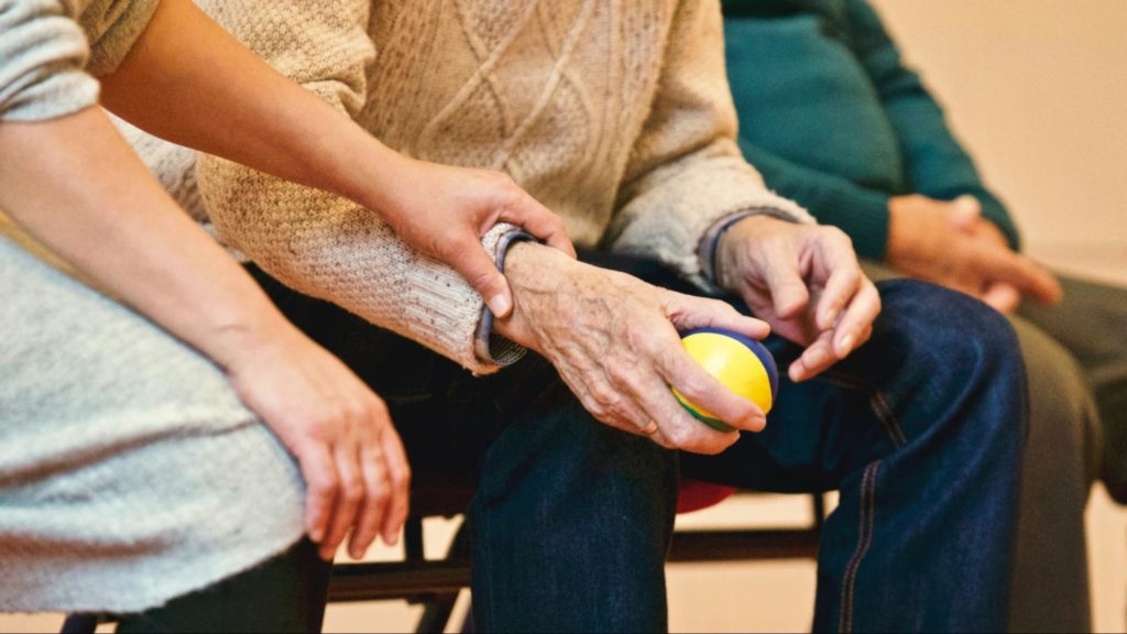 Elderly man supported by care worker holding a ball. Exercise for arthritis, Focus Care