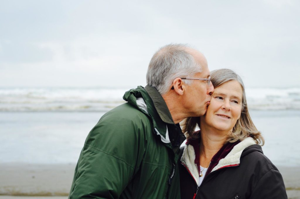 Happy older couple share a kiss on the beach. Dementia activities & Dementia Care - Focus Care